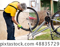 Man cleaning his bicycle for the new season 48835729