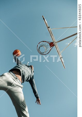 Low angle of a basketball player jumping 48844605