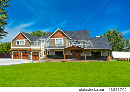 Brand new big farmer's house with three garage door and blue sky background 48851763