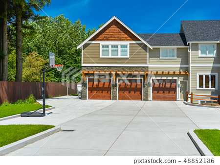 Brand new big farmer's house with three garage door and blue sky background 48852186