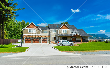 Brand new big farmer's house with three garage door and blue sky background 48852188