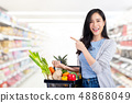 Asian woman with shopping basket full of groceries 48868049