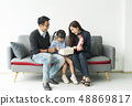 daughter holding present with father and mother 48869817