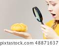 Shocked woman magnifying bun bread roll 48871637