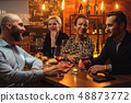 Group of friends having fun talk behind bar counter in a cafe 48873772