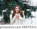 Girl brunette stands in winter in the park on a background of snowy Christmas trees. In his hand 48876341
