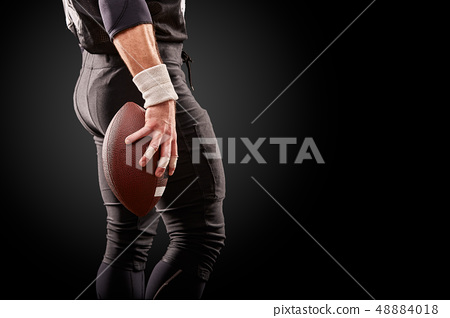 Mid section of American football player with ball against black, copy space, back view 48884018