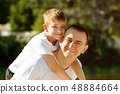 Happy father with little son on back outdoors. 48884664