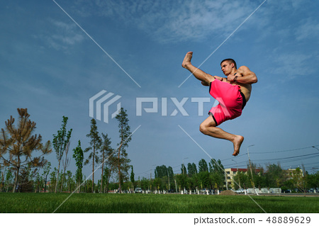 Tricking on lawn in park 48889629
