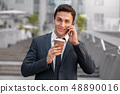 Morning refreshment. Businessman standing on the city street ddrinking coffee talking on smartphone 48890016