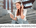 Young girl in headphones sitting on stairs in the city with smartphone listening music closed eyes 48890249