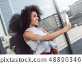 Young woman in the city street near window taking selfie on smartphone smiling cheerful side view 48890346