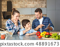 Family at home standing in kitchen together mother and son looking concentrated at father showing 48891673