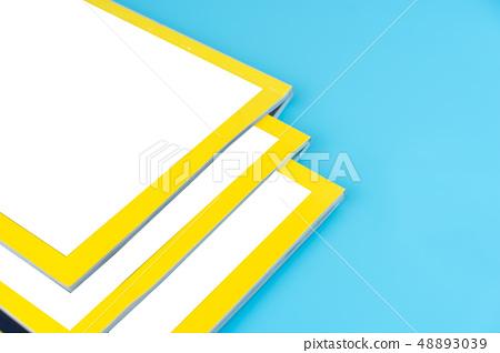 Stack magazines on blue background. 48893039