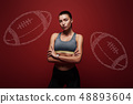 Fit looks good for every body. Young sportswoman standing with her arms crossed over red background. 48893604