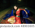 young pretty asian girl in bright colored interior on carpet 48903605