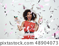 Portrait of a happy afro american woman in party hat holding glass of champagne and party whistle 48904073