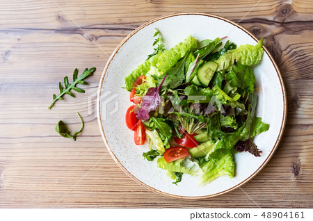 Bowl of salad with vegetables on wooden table. 48904161