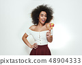 Sweet and beautiful. Cute and young afro american woman with curly hair looking at colorful lollipop 48904333