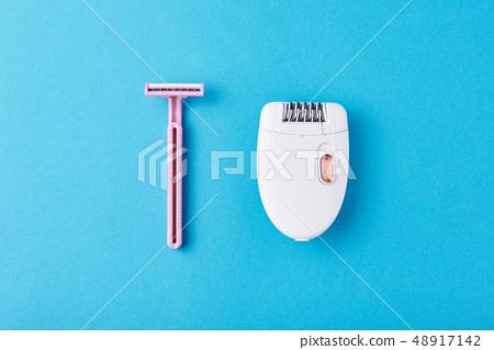 Epilator and razor fr shaving on blue background 48917142
