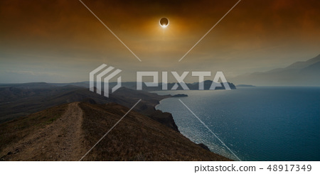Total solar eclipse in dark red sky above sea and 48917349