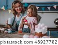 Smiling mother looking how her child dyeing eggs 48927782