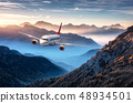 Airplane is flying over mountains in fog 48934501