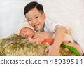 brother hugging newborn baby boy 48939514