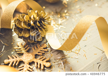 Golden shimmer Christmas decorating items on wood 48946775
