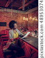 Beautiful Afro-American woman sitting at bar counter with papers 48953074