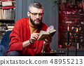 Bearded diviner sitting at the table with candles and enjoying self-education 48955213