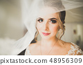 Gorgeous bride in robe posing and preparing for the wedding ceremony face in a room 48956309