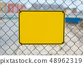 blank yellow sign on construction site fence - 48962319