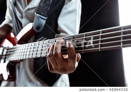 African American jazz musician playing bass guitar. 48964310