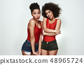 Pure beauty. Portrait of two cute and shy afro american women in jeans shorts are making a face 48965724