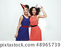 Birthday party! Two cute and young afro american women wearing summer dresses and party hats 48965739
