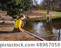 Happy child girl in bright yellow sweater paying with water outdoors 48967056