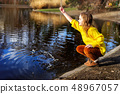 Happy child girl in bright yellow sweater paying with water outdoors 48967057