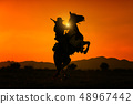 Silhouette Cowboy holding short gun and riding a 48967442