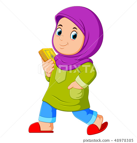 Moslem girl walking and carrying holy Quran 48978385