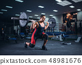 Weight lifter doing squats with a barbell in gym 48981676