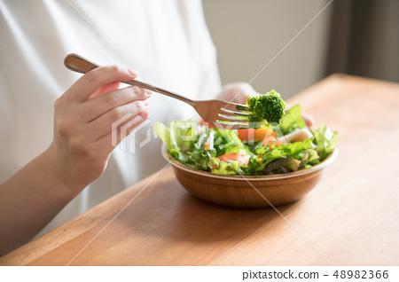 一個年輕的日本女人吃沙拉的手 48982366