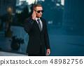 Male bodyguard uses security earpiece outdoors 48982756