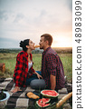 Couple eating croissants on picnic in summer field 48983099