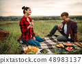 Love couple drinks wine, picnic on the meadow 48983137