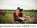 Woman with book lies on plaid, picnic in field 48983141