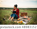 Young woman sitting on plaid and reads book 48983152