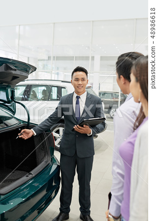 Salesman showing car trunk 48986618
