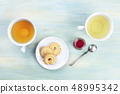 An overhead photo of tea, on a teal background with copy space 48995342