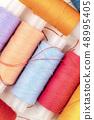 An overhead closeup photo of vibrant thread spools 48995405